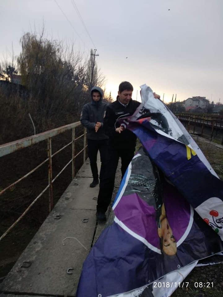 Луцькі муніципали зняли з моста обірваний рекламний плакат. ФОТО